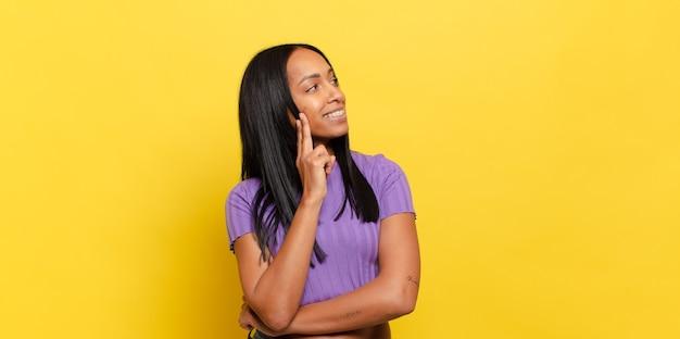 Jonge zwarte die gelukkig glimlacht en dagdroomt of twijfelt, kijkend naar de kant Premium Foto