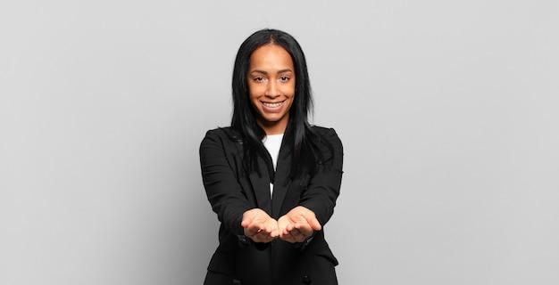 Jonge zwarte die gelukkig glimlacht met vriendelijke, zelfverzekerde, positieve blik, een object of concept aanbiedt en toont. bedrijfsconcept