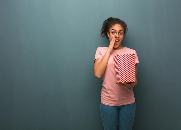 Jonge zwarte die iets gelukkig aan de voorzijde schreeuwt. ze houdt een emmer popcorns vast.
