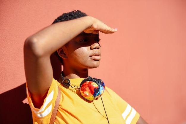 Jonge zwarte die met haar hand de zon behandelt die op haar ogen valt