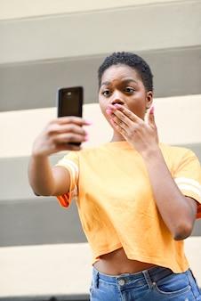 Jonge zwarte die selfie foto's met grappige uitdrukking in openlucht neemt.