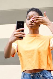 Jonge zwarte die selfie met grappige uitdrukking in openlucht neemt.