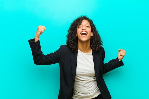 Jonge zwarte die triomfantelijk schreeuwt, kijkend als opgewekte, gelukkige en verraste winnaar, vierend tegen blauwe muur