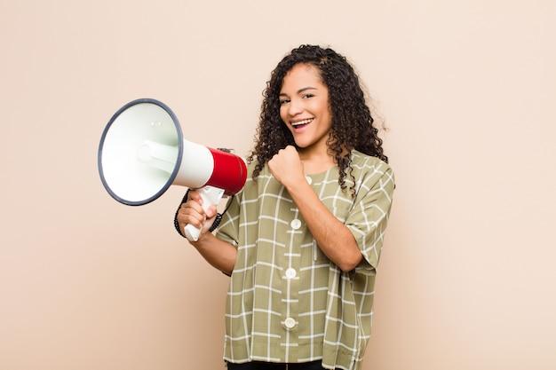 Jonge zwarte die zich gelukkig, positief en succesvol voelt, gemotiveerd wanneer ze voor een uitdaging staat of goede resultaten viert met een megafoon