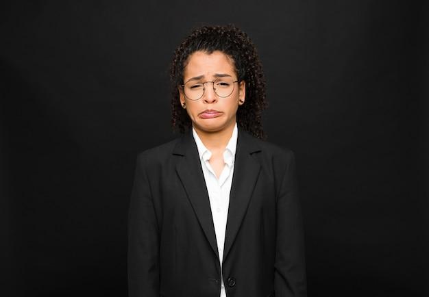 Jonge zwarte die zich verdrietig en jankend voelt met een ongelukkige blik, huilend met een negatieve en gefrustreerde houding op zwarte muur