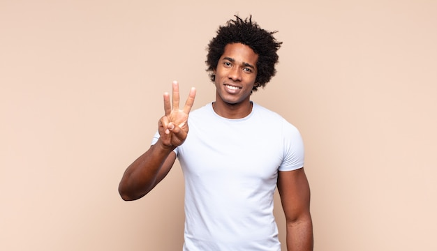 Jonge zwarte en afro-man die vriendelijk glimlacht kijkt, nummer vier of vierde met vooruit hand toont, aftellend