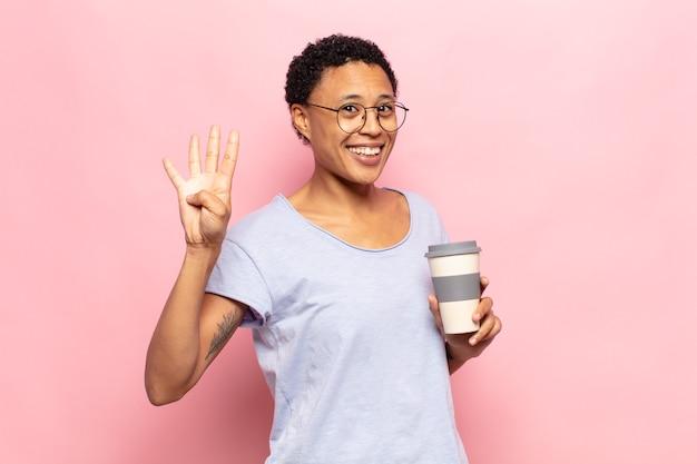 Jonge zwarte en afrovrouw die vriendelijk glimlacht kijkt, nummer vier of vierde met vooruit hand toont, aftellend