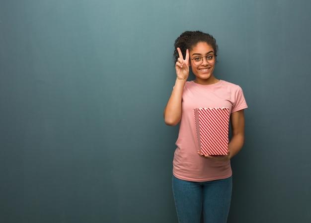 Jonge zwarte leuk en gelukkig doet een gebaar van overwinning. ze houdt een emmer popcorn vast.