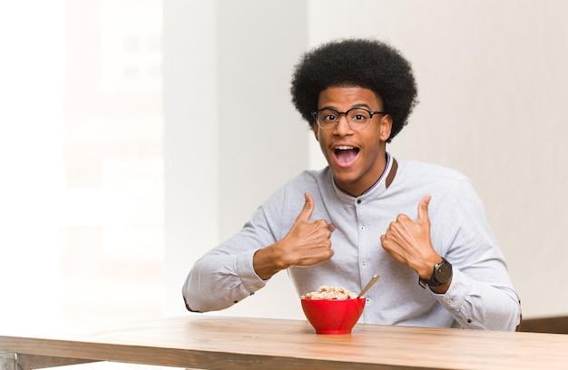 Jonge zwarte man aan het ontbijt verrast, voelt zich succesvol en welvarend