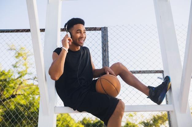 Jonge zwarte man aan het sporten, basketbal spelen, actieve levensstijl, zomerochtend, glimlachend gelukkig met plezier luisteren naar muziek op koptelefoon