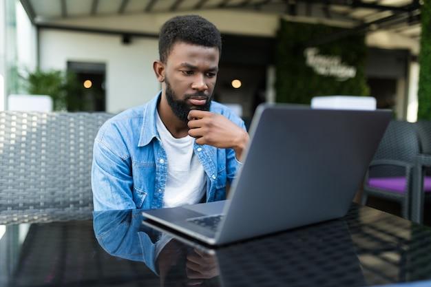 Jonge zwarte man aan het werk met laptop buiten een café op zoek naar camera