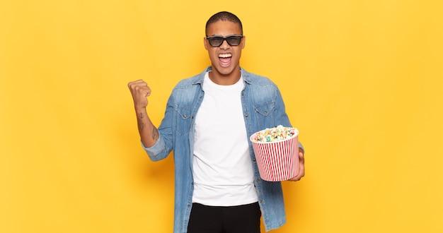 Jonge zwarte man agressief schreeuwen met een boze uitdrukking of met gebalde vuisten het vieren van succes