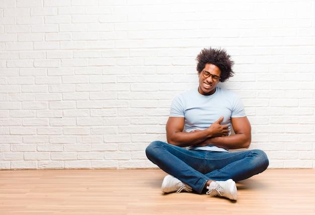 Jonge zwarte man angstig, ziek, ziek en ongelukkig voelen, lijden aan een pijnlijke buikpijn of griep zittend op de vloer thuis