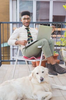 Jonge zwarte man binnenzittinglaag die laptop computer en slimme telefoon met behulp van