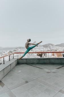 Jonge zwarte man dansen op het dak van een gebouw
