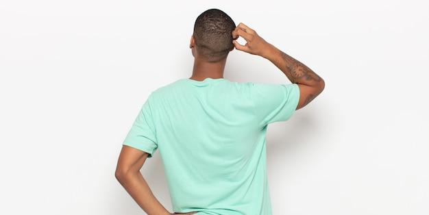 Jonge zwarte man denken of twijfelen, hoofd krabben, zich verbaasd en verward voelen
