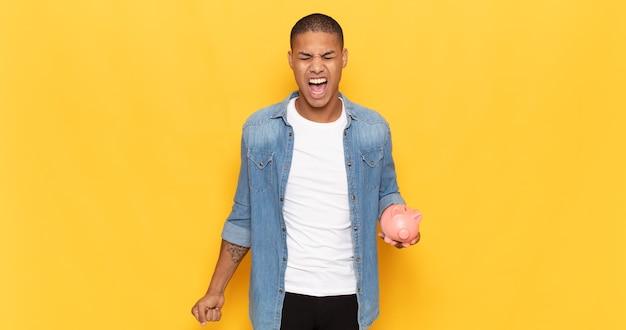 Jonge zwarte man die agressief schreeuwt, erg boos, gefrustreerd, verontwaardigd of geïrriteerd kijkt, nee schreeuwt