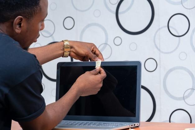 Jonge zwarte man die de webcam van zijn laptop opneemt