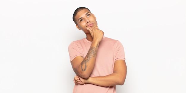 Jonge zwarte man die denkt, zich twijfelachtig en verward voelt, met verschillende opties, zich afvraagt welke beslissing hij moet nemen