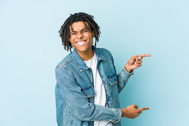 Jonge zwarte man die een jeansjasje draagt dat met wijsvingers naar een exemplaarruimte richt, opwinding en verlangen uitdrukt.