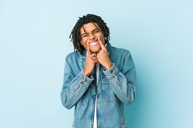 Jonge zwarte man die een jeansjasje draagt en een valse glimlach doet