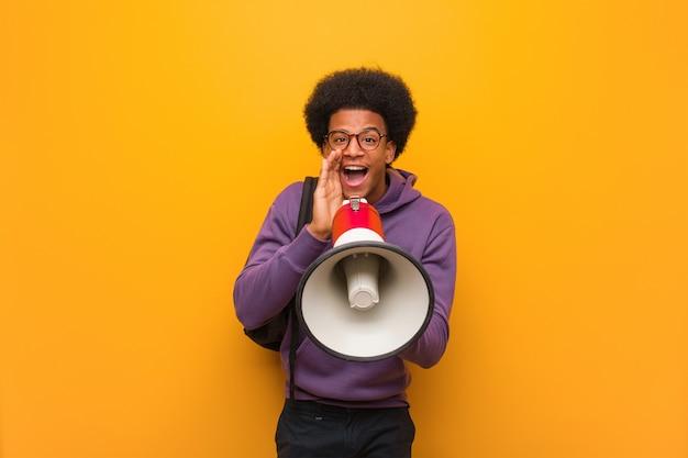 Jonge zwarte man die een megafoon vasthoudt die iets blij aan de voorkant schreeuwt
