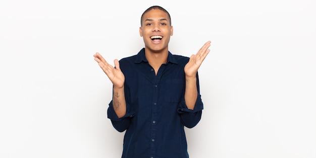 Jonge zwarte man die er blij en opgewonden uitziet, geschokt door een onverwachte verrassing met beide handen open naast het gezicht