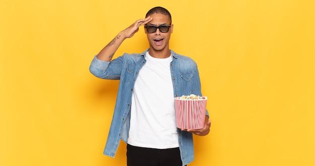 Jonge zwarte man die er blij, verbaasd en verrast uitzag, lachte en zich verbluffend en ongelooflijk goed nieuws realiseerde