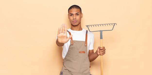 Jonge zwarte man die er serieus, streng, ontevreden en boos uitziet met een open palm die een stopgebaar maakt