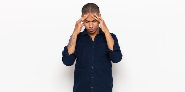 Jonge zwarte man die gestrest en gefrustreerd kijkt, onder druk werkt met hoofdpijn en last heeft van problemen