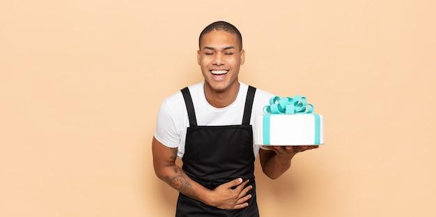 Jonge zwarte man die hardop lacht om een hilarische grap