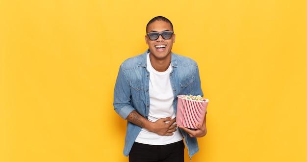 Jonge zwarte man die hardop lacht om een of andere hilarische grap, zich gelukkig en opgewekt voelt, plezier heeft