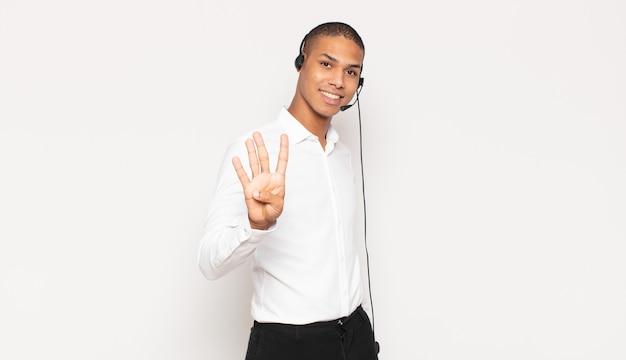 Jonge zwarte man die lacht en er vriendelijk uitziet, nummer vier of vierde toont met de hand naar voren, aftellend