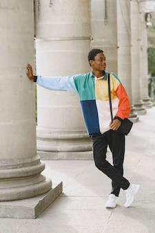 Jonge zwarte man die lacht in stedelijke stad. gemengde man in een kleurrijke trui.