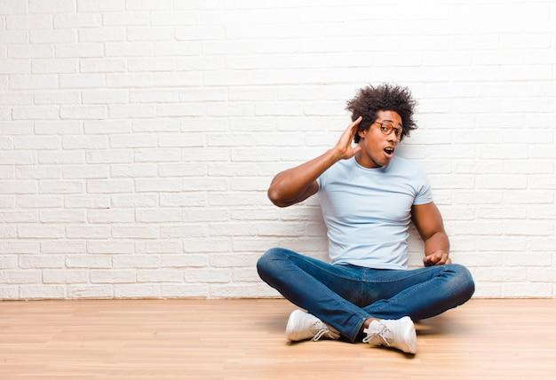 Jonge zwarte man die lacht, nieuwsgierig naar de zijkant kijkt, probeert te luisteren naar roddel of een geheime zitting thuis op de vloer hoort
