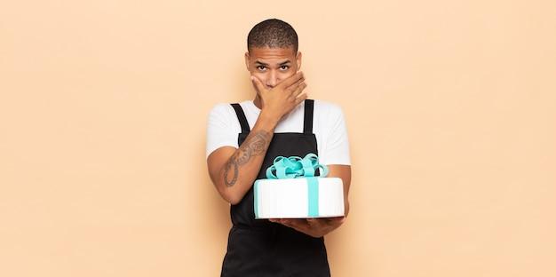 Jonge zwarte man die mond bedekt met handen met een geschokte, verbaasde uitdrukking, een geheim bewaren of oeps zeggen