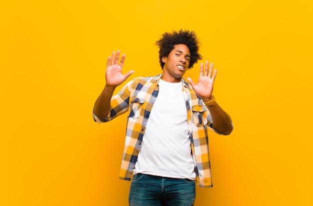 Jonge zwarte man die nerveus, angstig en bezorgd kijkt en niet mijn schuld zegt of ik heb het niet tegen de oranje muur gedaan