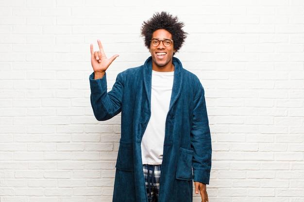 Jonge zwarte man die pyjama's draagt met een jurk die zich gelukkig, leuk, zelfverzekerd, positief en opstandig voelt, en rock of heavy metal-bord met de hand maakt tegen de bakstenen muur