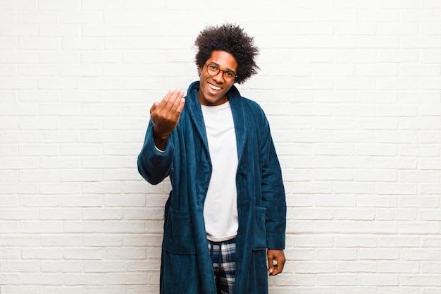 Jonge zwarte man die pyjama's draagt met een jurk die zich gelukkig, succesvol en zelfverzekerd voelt, voor een uitdaging staat en zegt: kom maar op! of je verwelkomen tegen een bakstenen muur