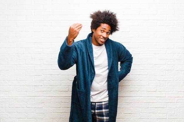 Jonge zwarte man die pyjama's draagt met toga die kapsel of geldgebaar maakt en zegt dat je je schulden moet betalen! tegen baksteen