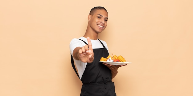 Jonge zwarte man die trots en zelfverzekerd glimlacht en nummer één triomfantelijk laat poseren, zich als een leider voelt