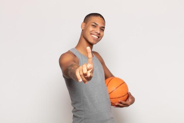 Jonge zwarte man die trots en zelfverzekerd glimlacht en nummer één triomfantelijk laat poseren, zich een leider voelt