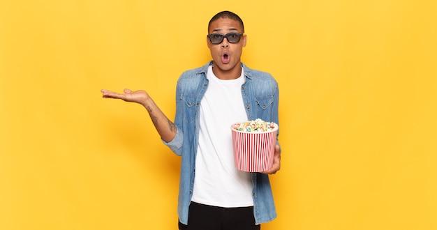Jonge zwarte man die verbaasd en geschokt kijkt, met open mond een voorwerp vasthoudend met een open hand aan de zijkant