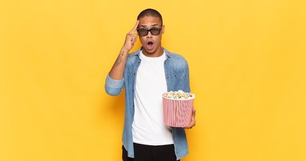 Jonge zwarte man die verbaasd, met open mond, geschokt kijkt, een nieuwe gedachte, idee of concept realiseert