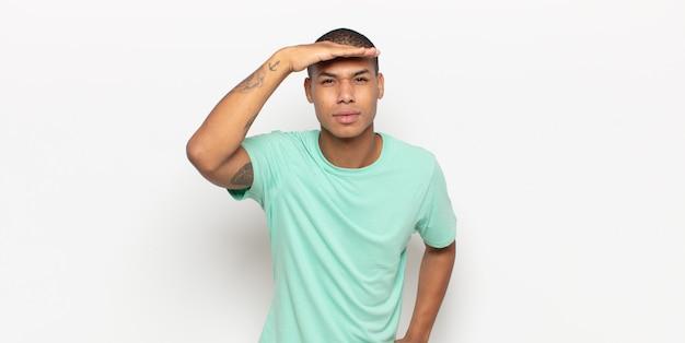 Jonge zwarte man die verbijsterd en verbaasd kijkt, met hand over voorhoofd ver weg kijkend, kijkend of zoekend