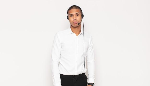 Jonge zwarte man die verdrietig en zeurderig is met een ongelukkige blik, huilen met een negatieve en gefrustreerde houding
