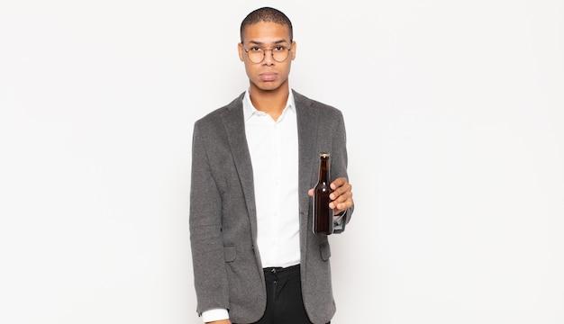 Jonge zwarte man die verdrietig en zeurderig was met een ongelukkige blik, huilend met een negatieve en gefrustreerde houding