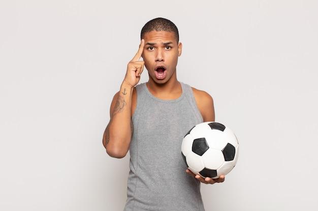 Jonge zwarte man die verrast, met open mond, geschokt kijkt en een nieuwe gedachte, idee of concept realiseert