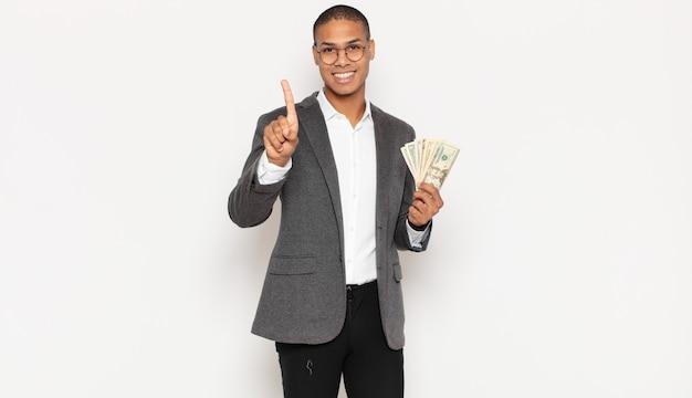 Jonge zwarte man die vriendelijk glimlacht en kijkt, nummer één toont of eerst met vooruit hand, aftellend