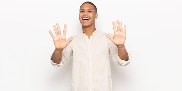 Jonge zwarte man die vriendelijk glimlacht en kijkt, nummer tien of tiende met vooruit hand toont, aftellend